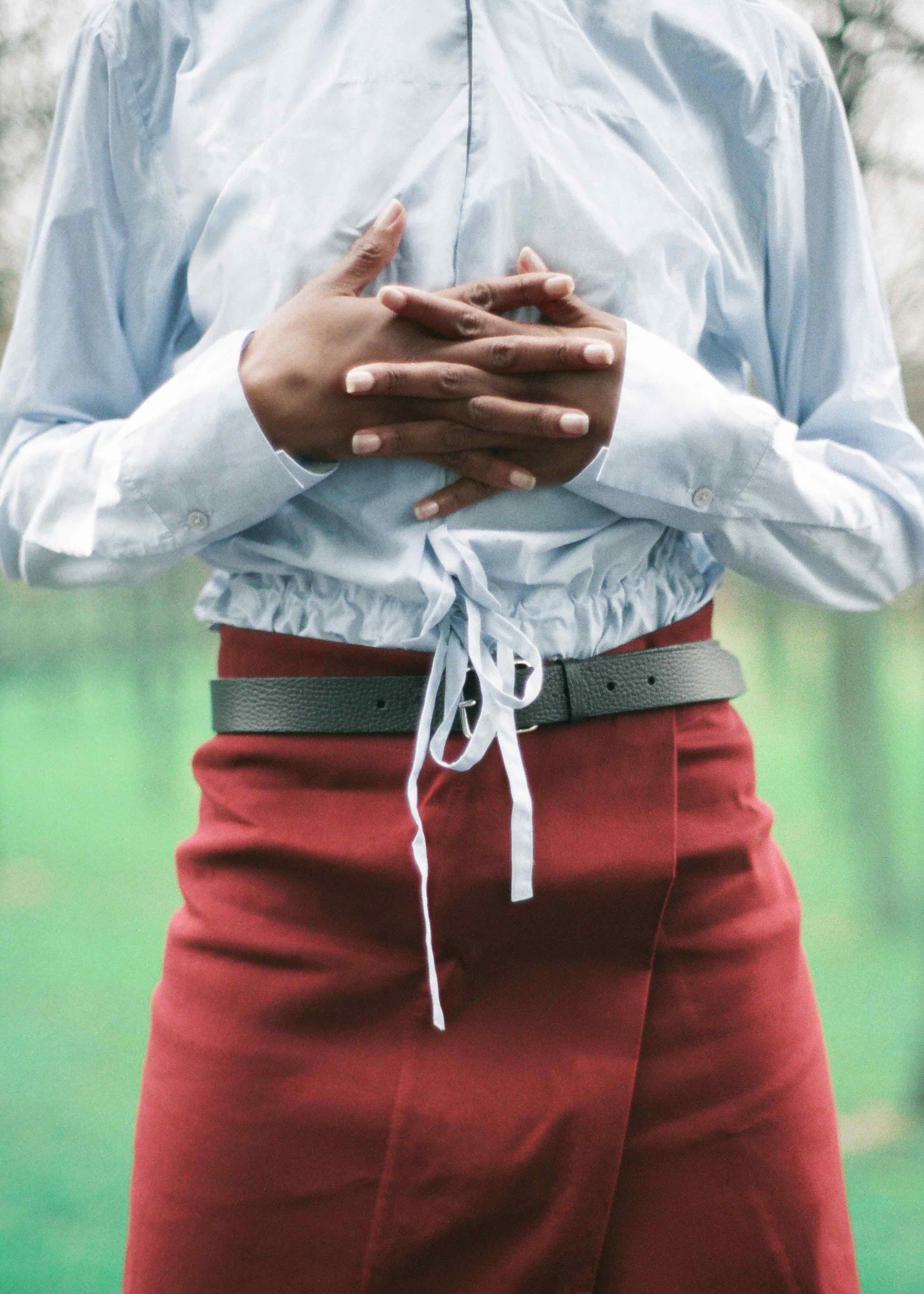 Blue cotton poplin shirt, cotton gabardine wrap skirt, calf leather belt.
