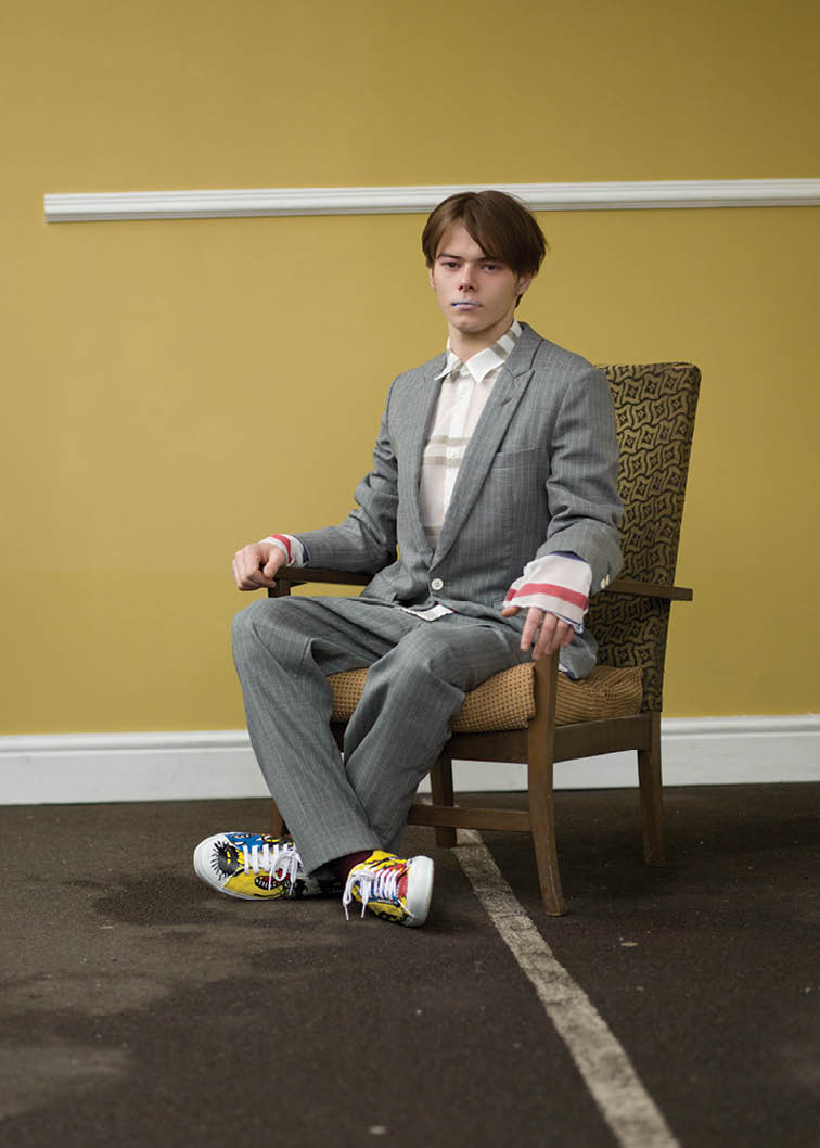 Striped mohair and wool grey jacket, white shirt with multicolored stripes, striped grey pants and hand painted canvas plimsolls.