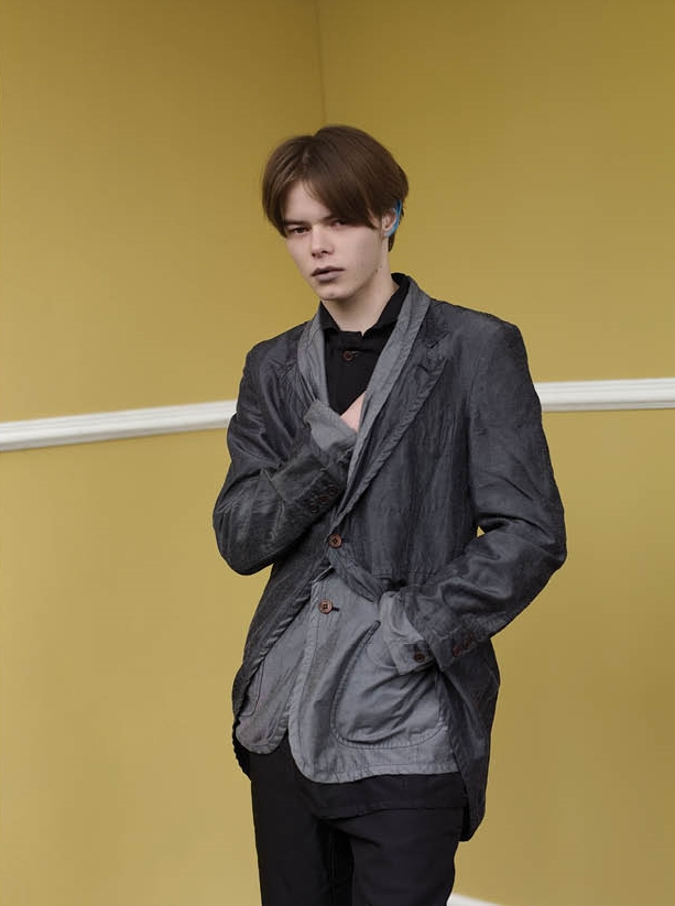 Double-layered jacket in treated fabrics, black cotton shirt and pleated shorts.