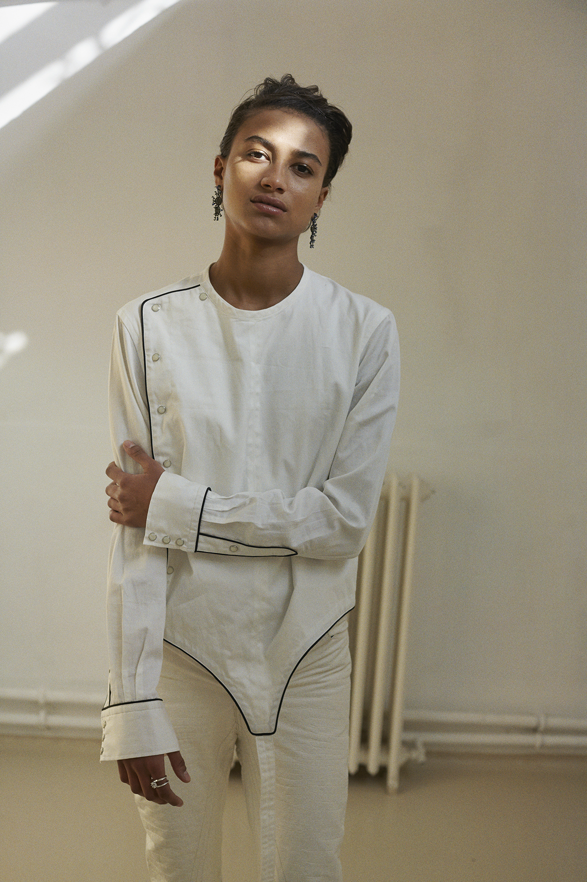 Fencing shirt with piping cord, leather pants. Long drop earrings and hand-cut stone silver ring EDDIE BORGO