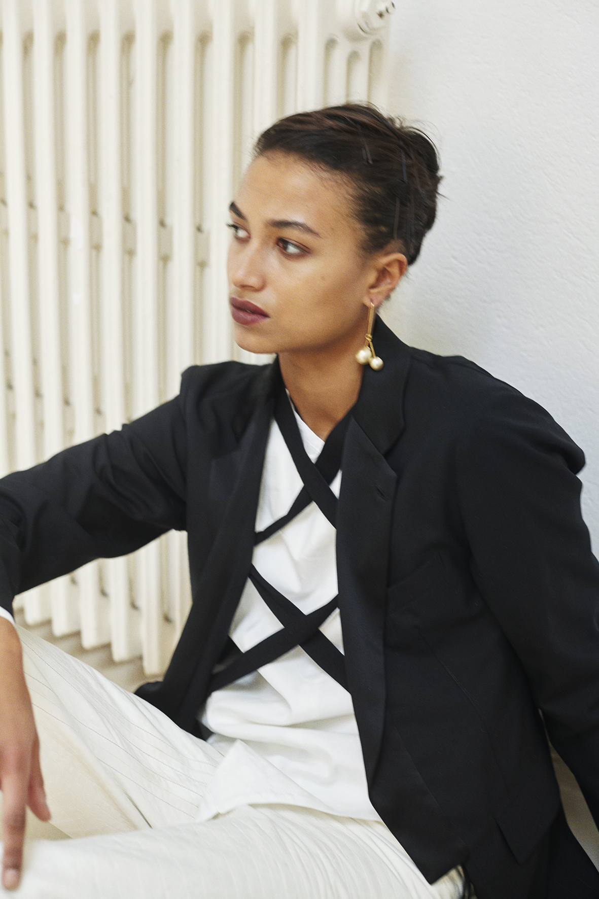 Tailored wool jacket, fencing shirt, leather pants. Ivory gold pearl earrings CÉLINE
