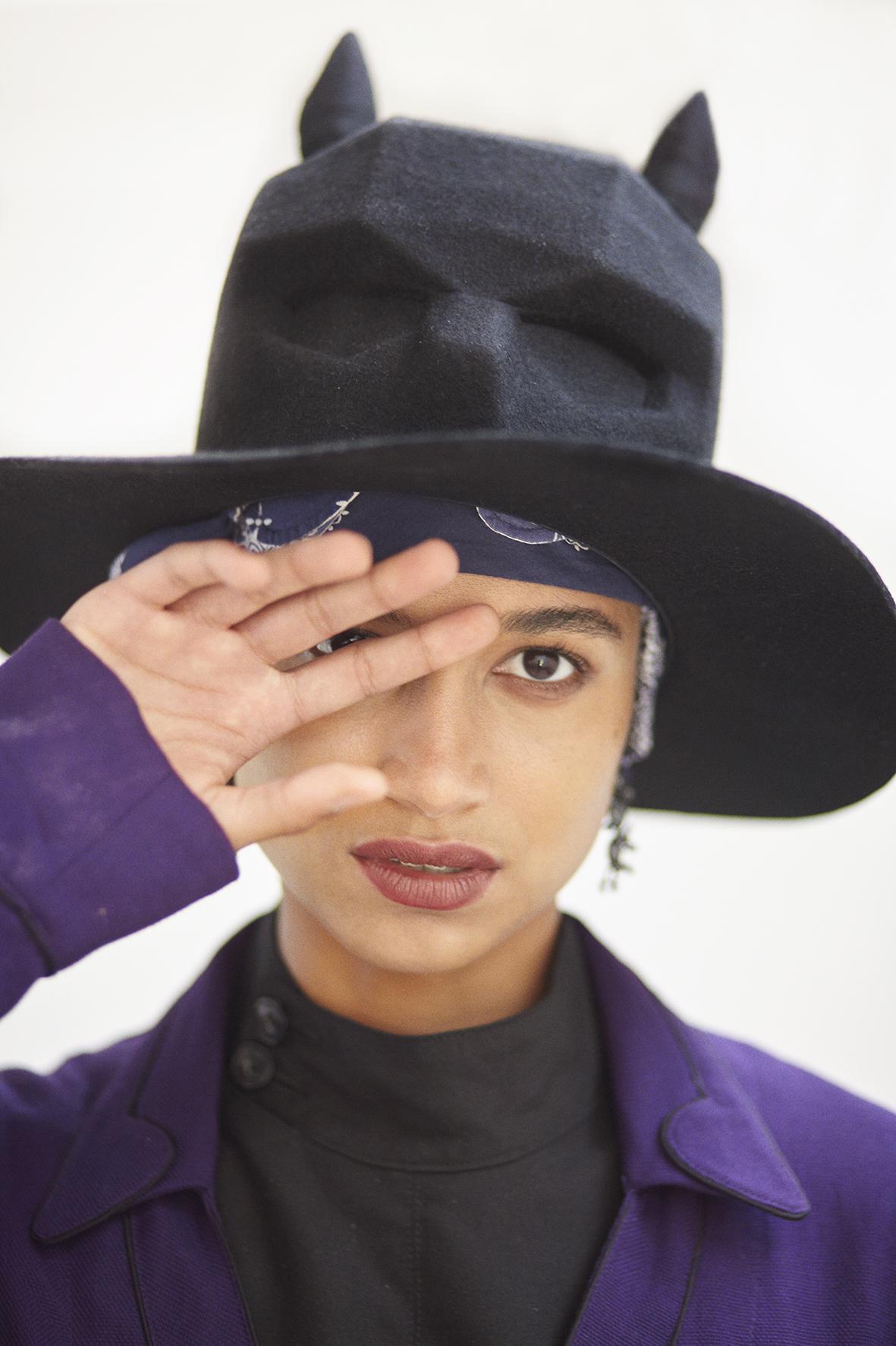 Felt wool skull hat, mask bandana, cotton jacket, croise fencing jacket in black. Long drop earrings EDDIE BORGO