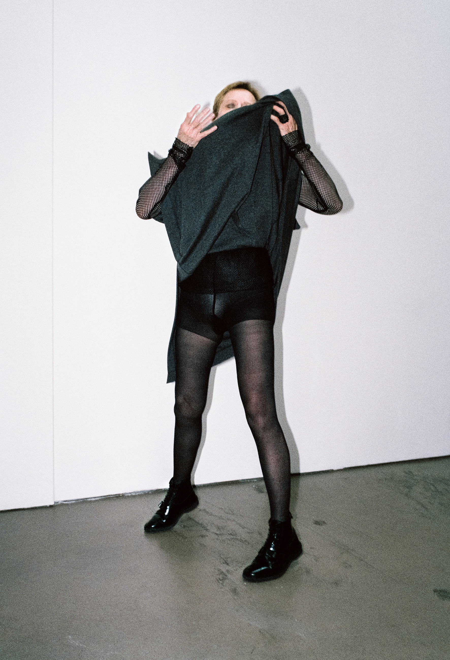 Grey wool dress, fishnet turtleneck, patent leather lace-up shoes, oversize ring. Black tights WOLFORD