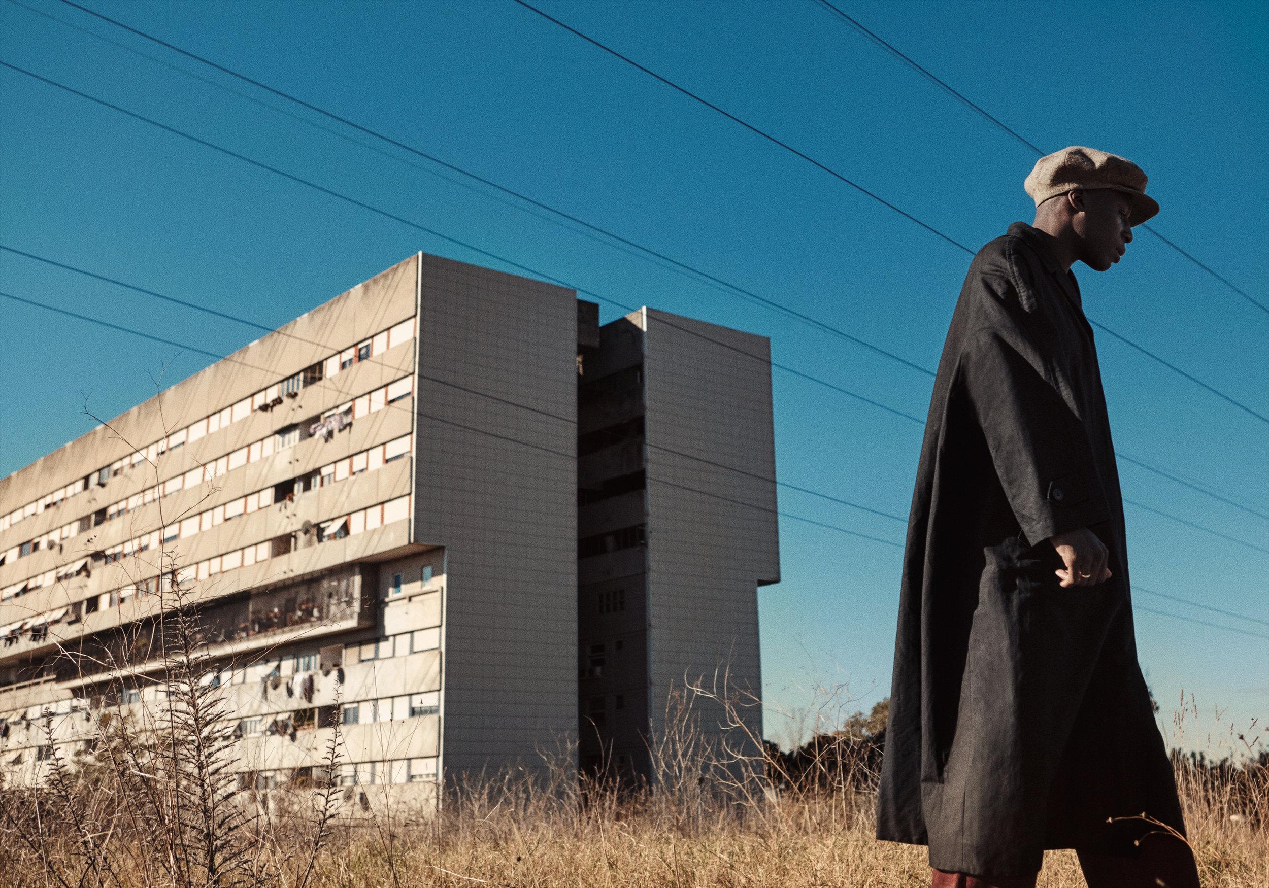 Black linen coat DRIES VAN NOTEN, burgundy trousers PAL ZILERI, wool tweed flat cap LOCK & CO HATTERS.