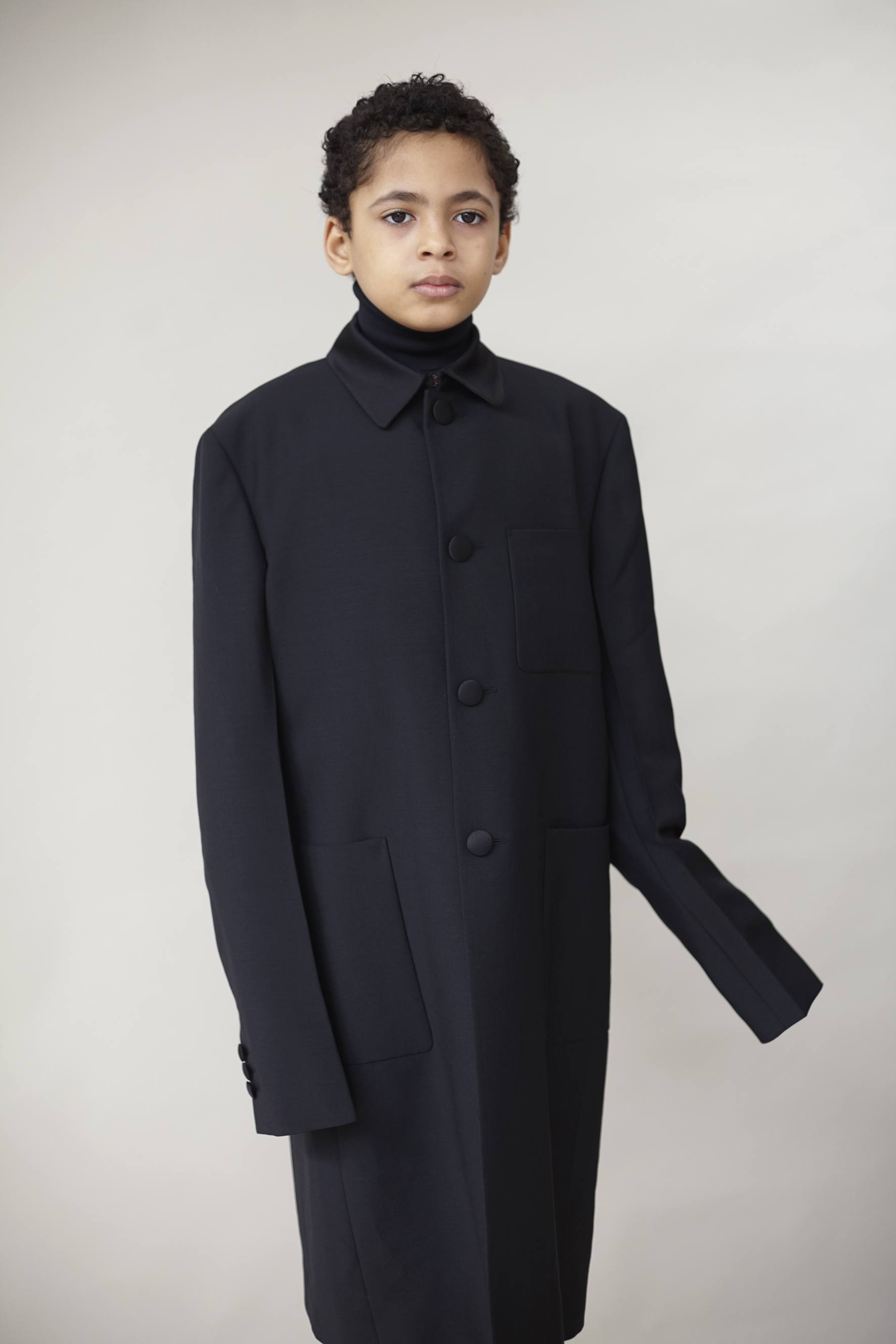 Black wool and satin coat and technical jersey turtleneck PRADA, white velvet tights WOLFORD.