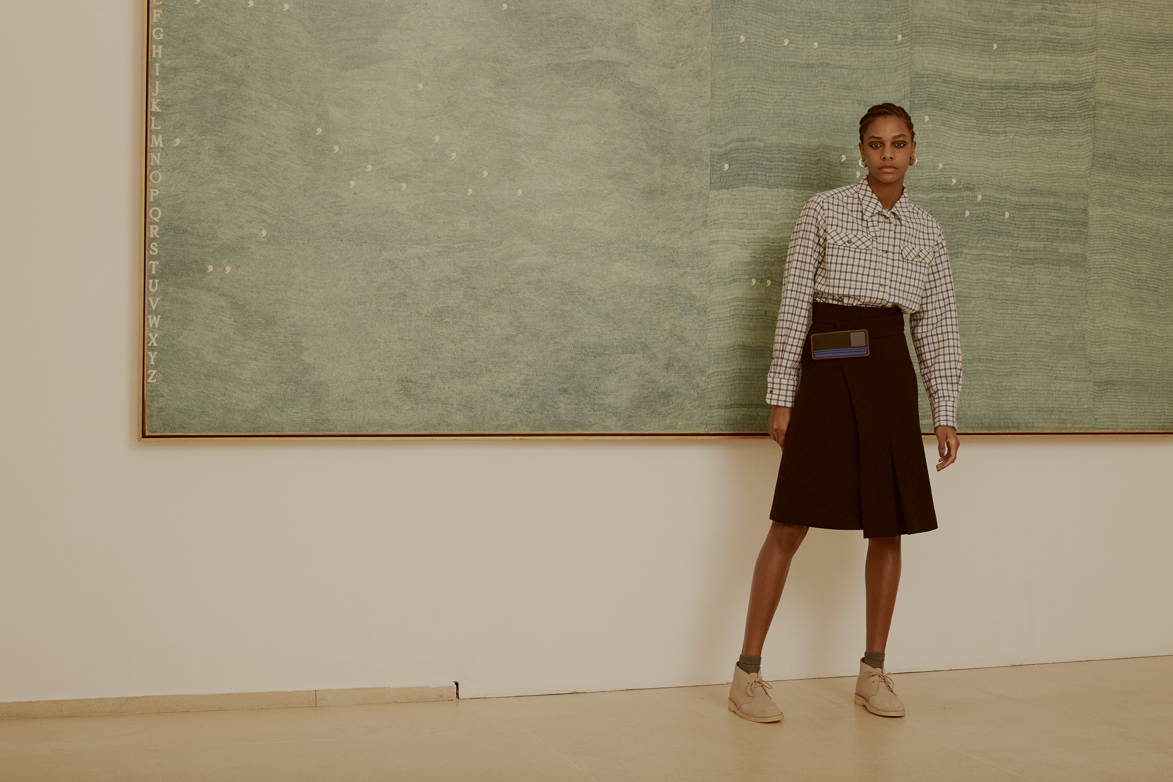 Alighiero Boetti, Mettere al mondo il mondo, 1975.   Rubber strap wrap skirt PRADA, wool checkered shirt HOLLAND & HOLLAND, silver brass earrings CÉLINE, silk socks MARIA LA ROSA, suede desert boots CLARKS