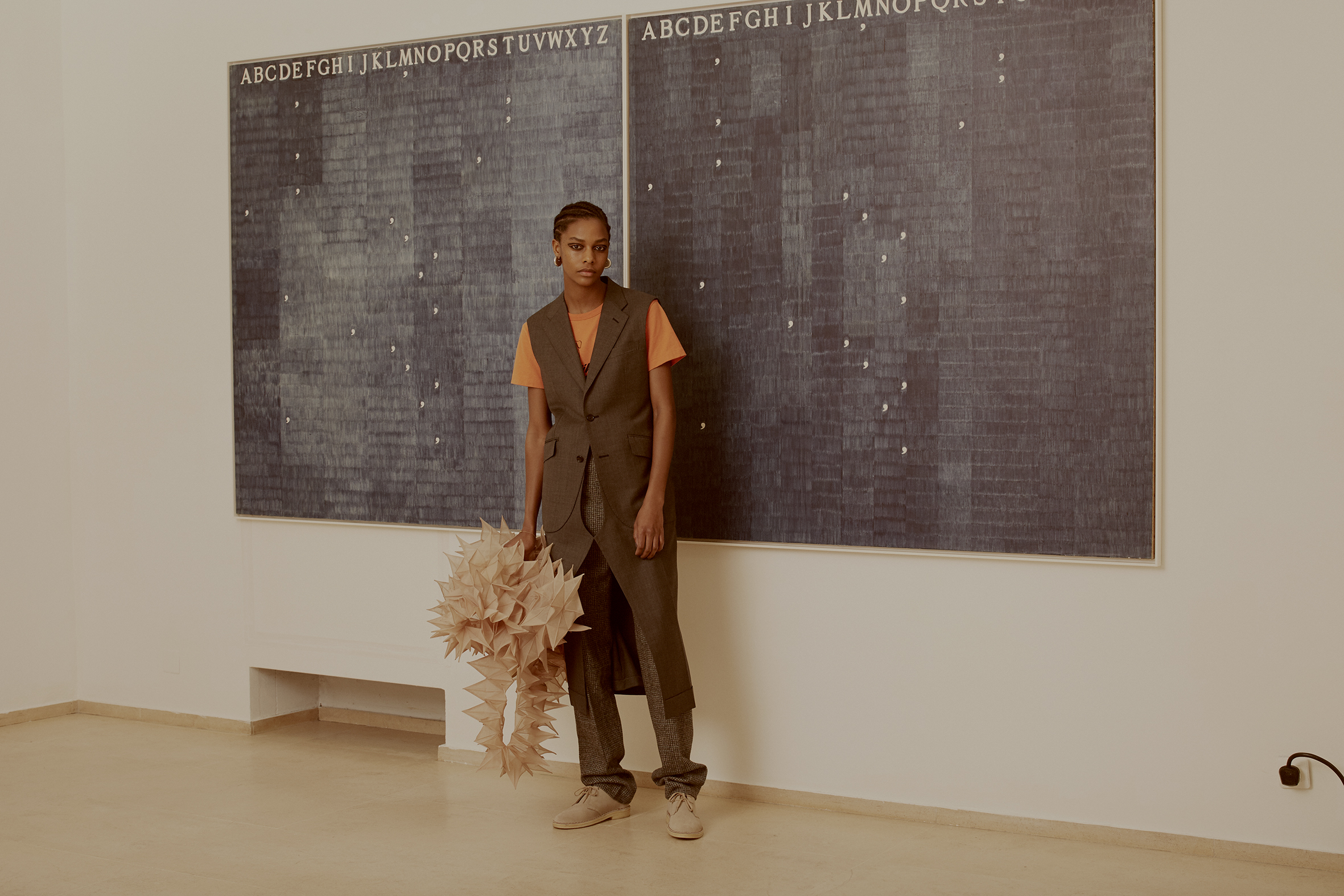Alighiero Boetti, Mettere al mondo il mondo, 1972-73.  Wool long tunic waistcoat, orange printed t-shirt and three dimensional spikes dress JUNYA WATANABE COMME DES GARÇONS, wool tweed trousers HOLLAND & HOLLAND, silver brass earrings CÉLINE,suede desert boots CLARKS