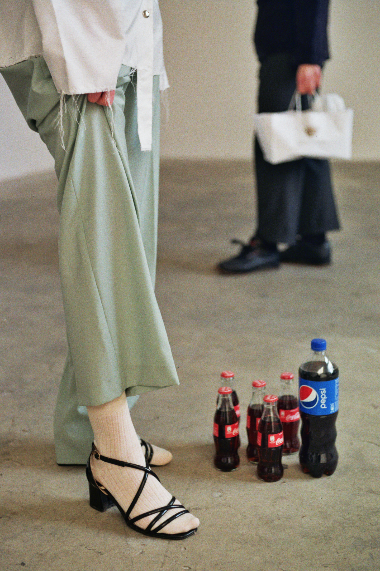 White organza shirt: Traffico, light wool trousers: Pence1979, socks: Maria La Rosa, sandals: stylist own.  Art piece: Rebel Rebel   1lt of Pepsi in 5 bottles of Coca - Cola and 1lt of Coca-Cola in one bottle of Pepsi  Artist: Roberto Fassone