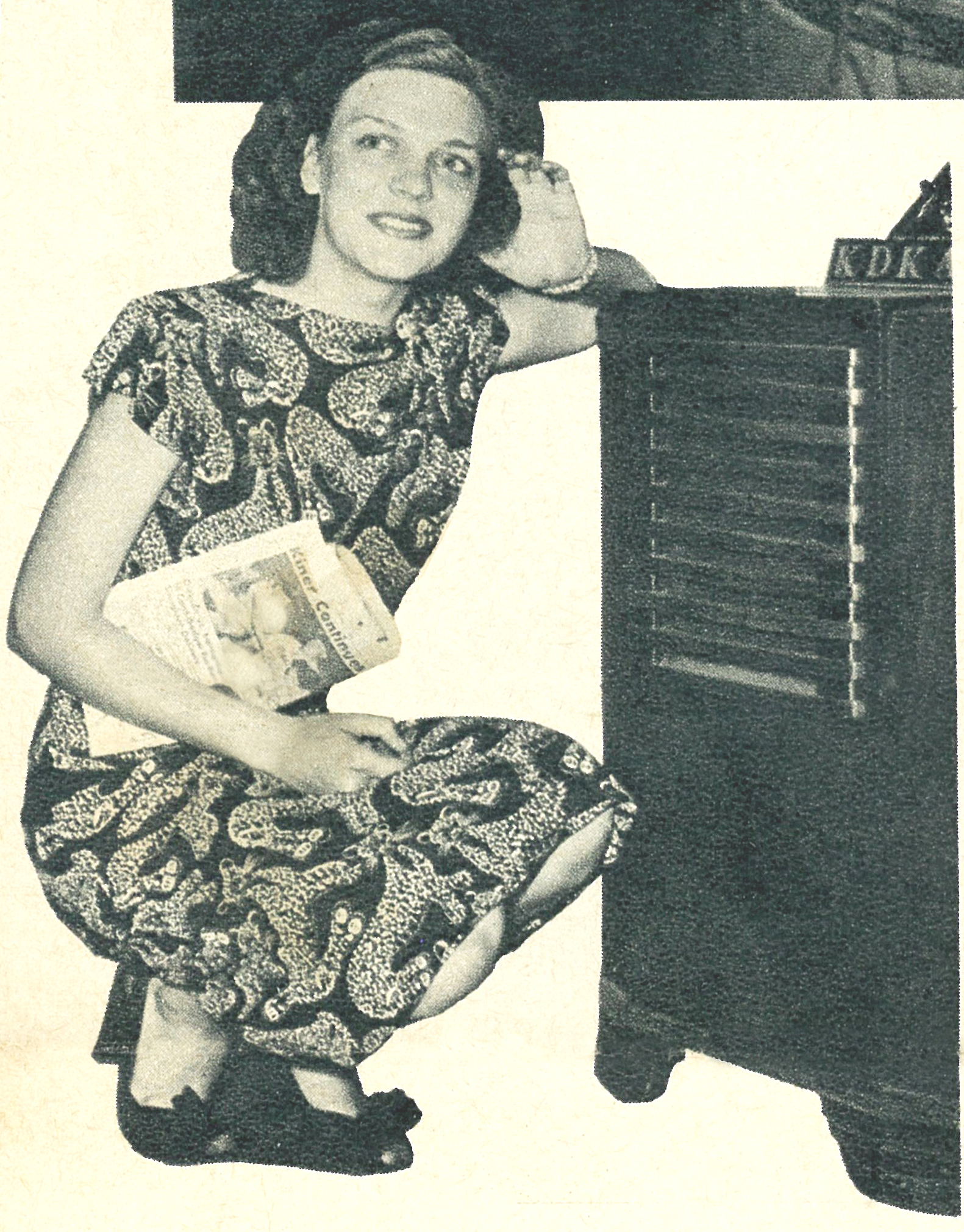 BLO-Kneeling next to radio with sports section.jpg