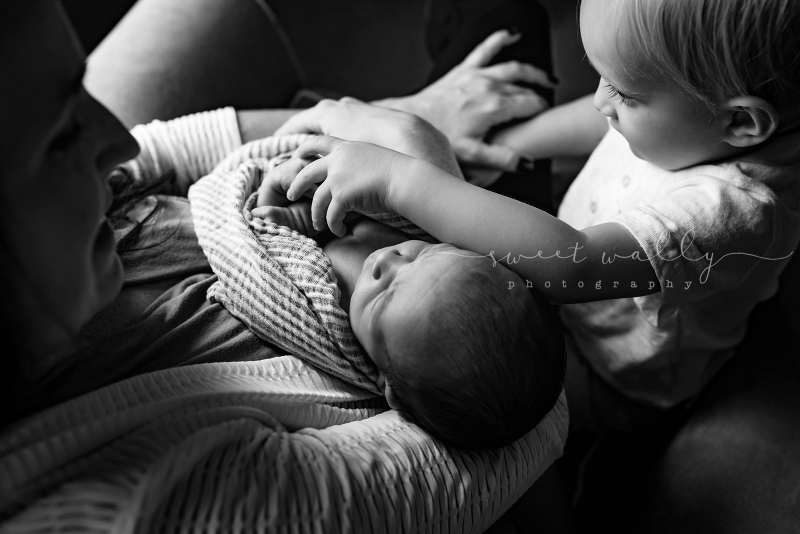 Big brother checking out the new kid in town | Relaxed family newborn photos by Sweet Wally Photography in Nashville, Tenneessee