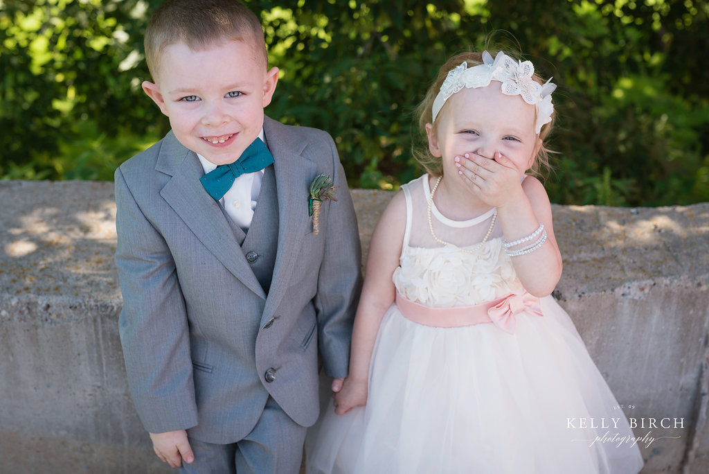 Adorable flower girl giggling iwth a headband and pearls and ring bearer in a suit and bowtie holding hands