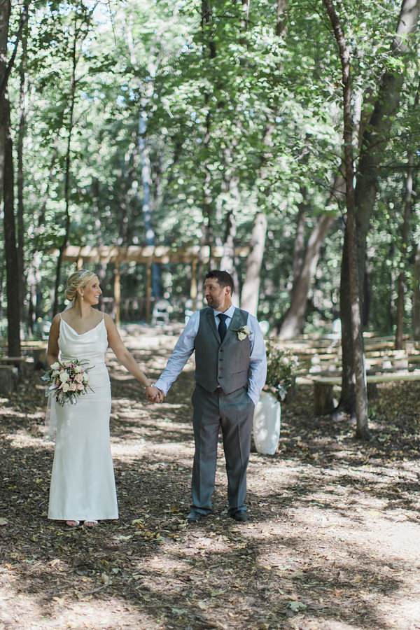 bridal gown with straps and a v plunging back, beaded veil with low hair twist | walking in the orchards | groom in a vest | Ashley Elwill Minneapolis Wedding Photographer