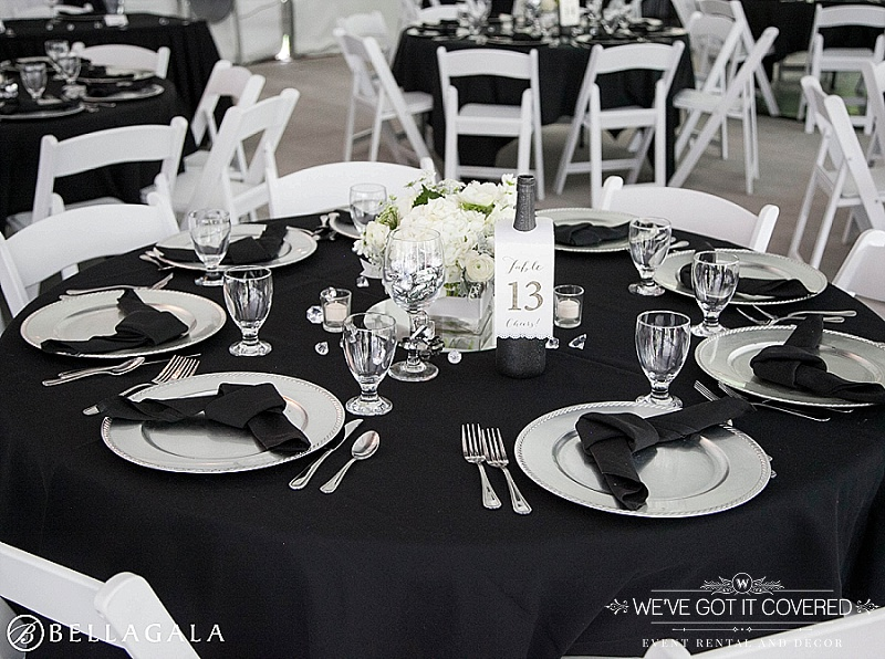 black knot napking fold on silver chargers with black table linen and white garden chairs in a tent wedding with votives and champagne table numbers | We've Got it Covered