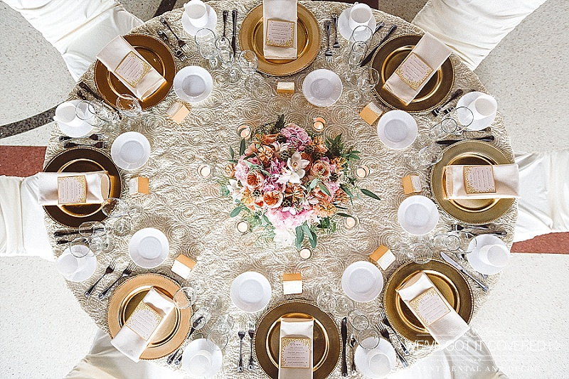 white napkins on gold beaded chargers with aplique table linen in ivory | votives with a pink and orange centerpiece | chair covers | We've Got it Covered