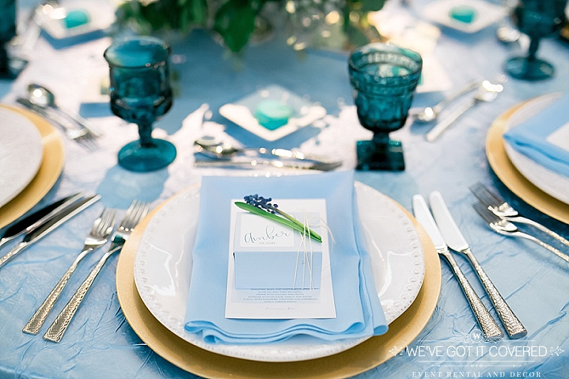 baby blue napkin on white beaded dinner plate with gold charger and blue tinted glassware on top of blue crush table linen | menu with name card on top and tied with lavender | We've Got it Covered