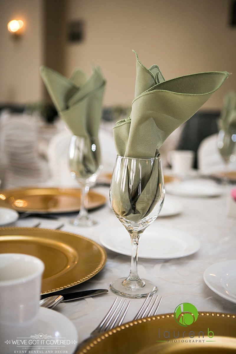 Sage green napkins in flame fold in wine glass with gold beaded chargers on white table cloth with see through overlay | We've Got it Covered | Photo by Lauren B Photography