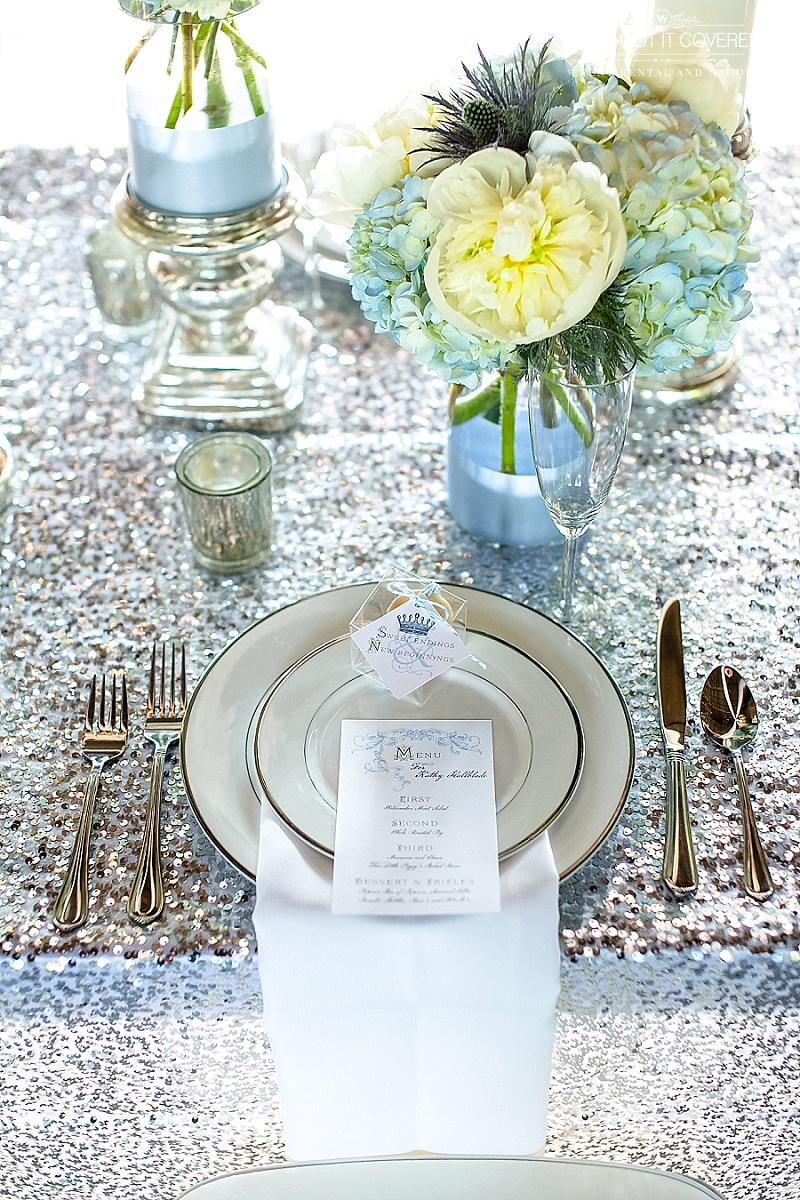 champagne sequin table cloth with white drop fold napkin | menu and wedding favors on top of salad plate | silver mercury votives | candle pillars with blue dipped vases | floral bouquets with thistle, blue antique hydrangea and white peony | We've Got it Covered