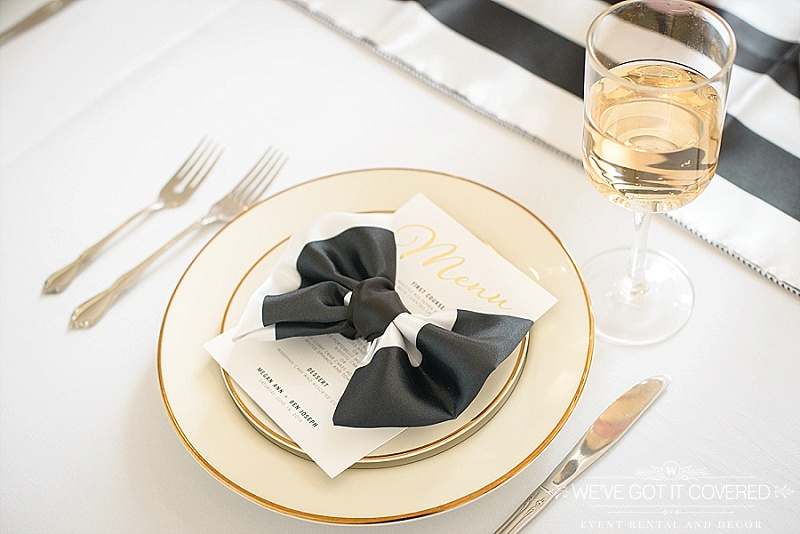 black and white napkin in bow tie fold on top of menu with gold foil | gold rimmed dinner and salad plate | black and white table runner | We've Got it Covered