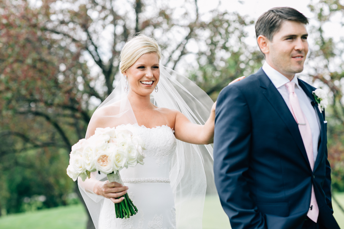 First look photo | Mark Fierst Photography | Sadie's Floral | Acowsay Cinema | Wayzata Country Club | groom in pink tie | white rose bouquet | Sixpence blog