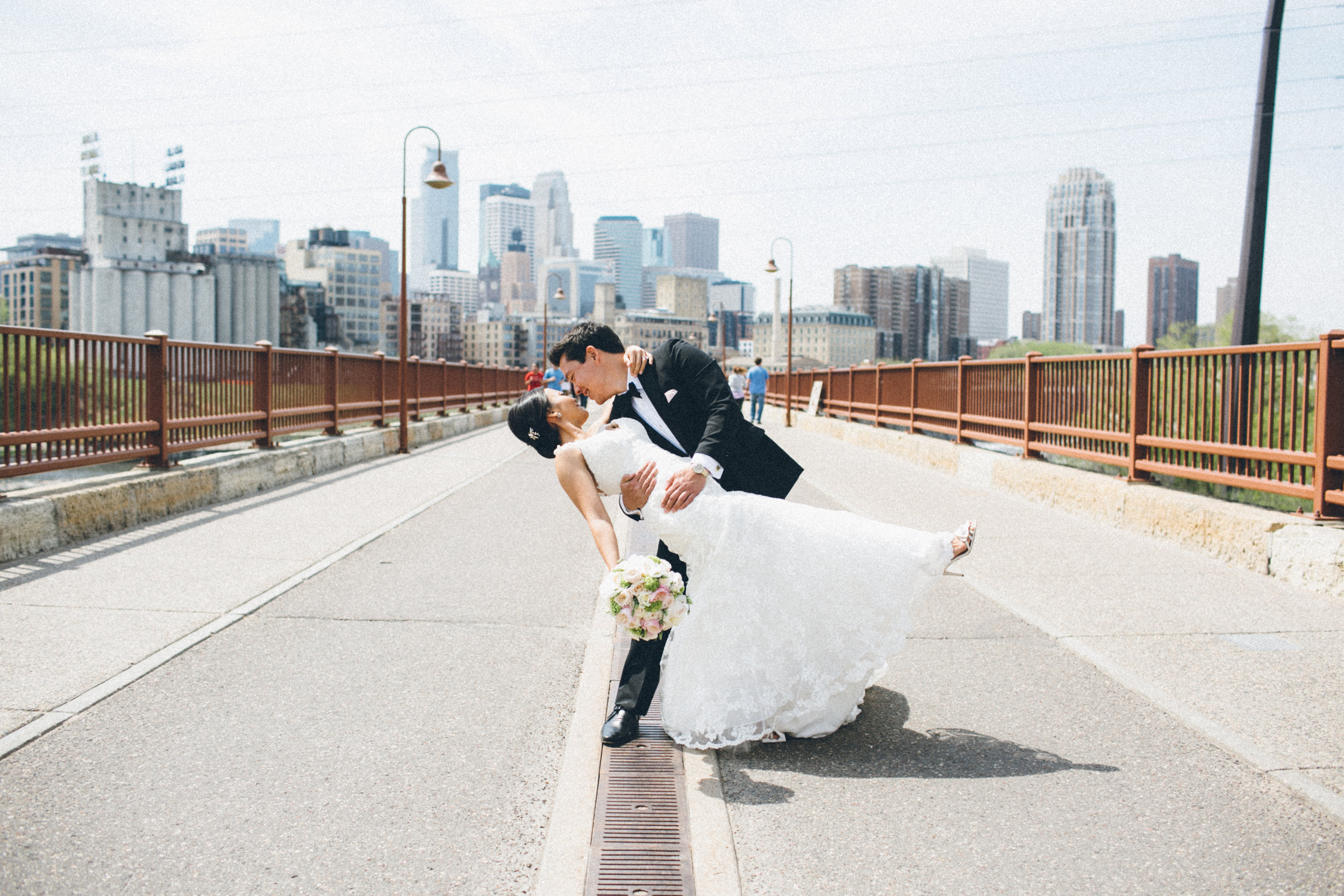 Mark Fierst Minneapolis Wedding Photographer | Sixpence Standard blog post | dip kiss on the bride with the city in the backdrop