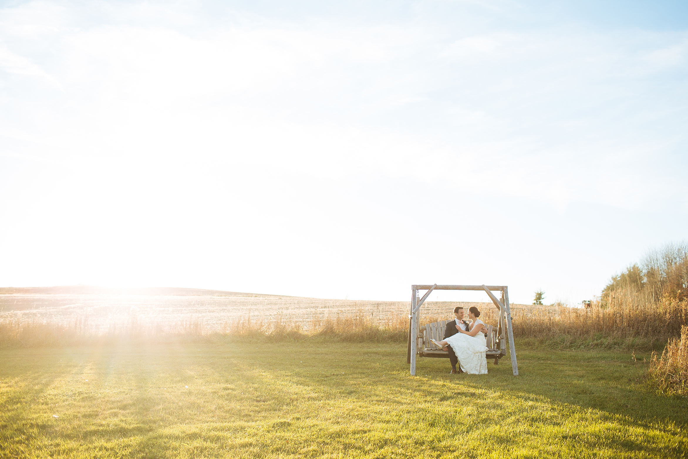 Alyssa Lee Minneapolis Wedding Photographer | Sixpence Standard wedding blog | bride and groom kissing in a field of grassy field on a swing