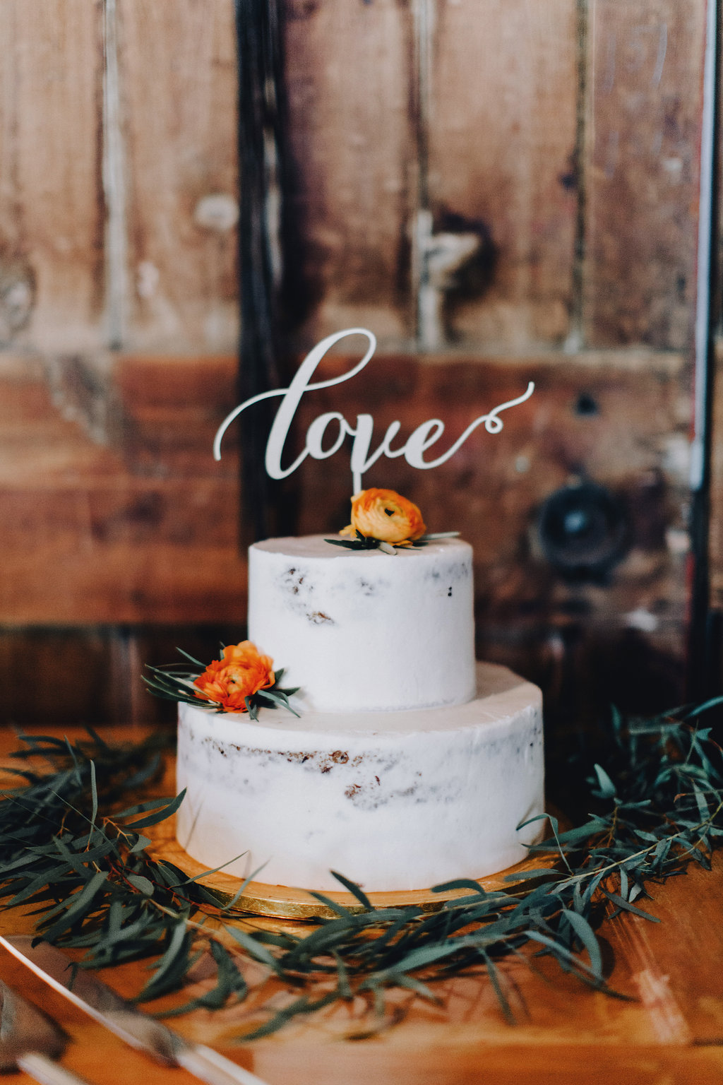 love laser cut cake topper, two tier with orange ranunculus | Acowsay Videography | Matt Lien Photography | Sixpence Standard Wedding Blog
