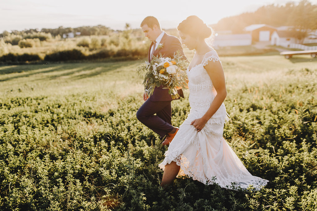 bride and groom walking in the grassy field, bride with cap sleeved lace dress  | Acowsay Videography | Matt Lien Photography | Sixpence Standard Wedding Blog