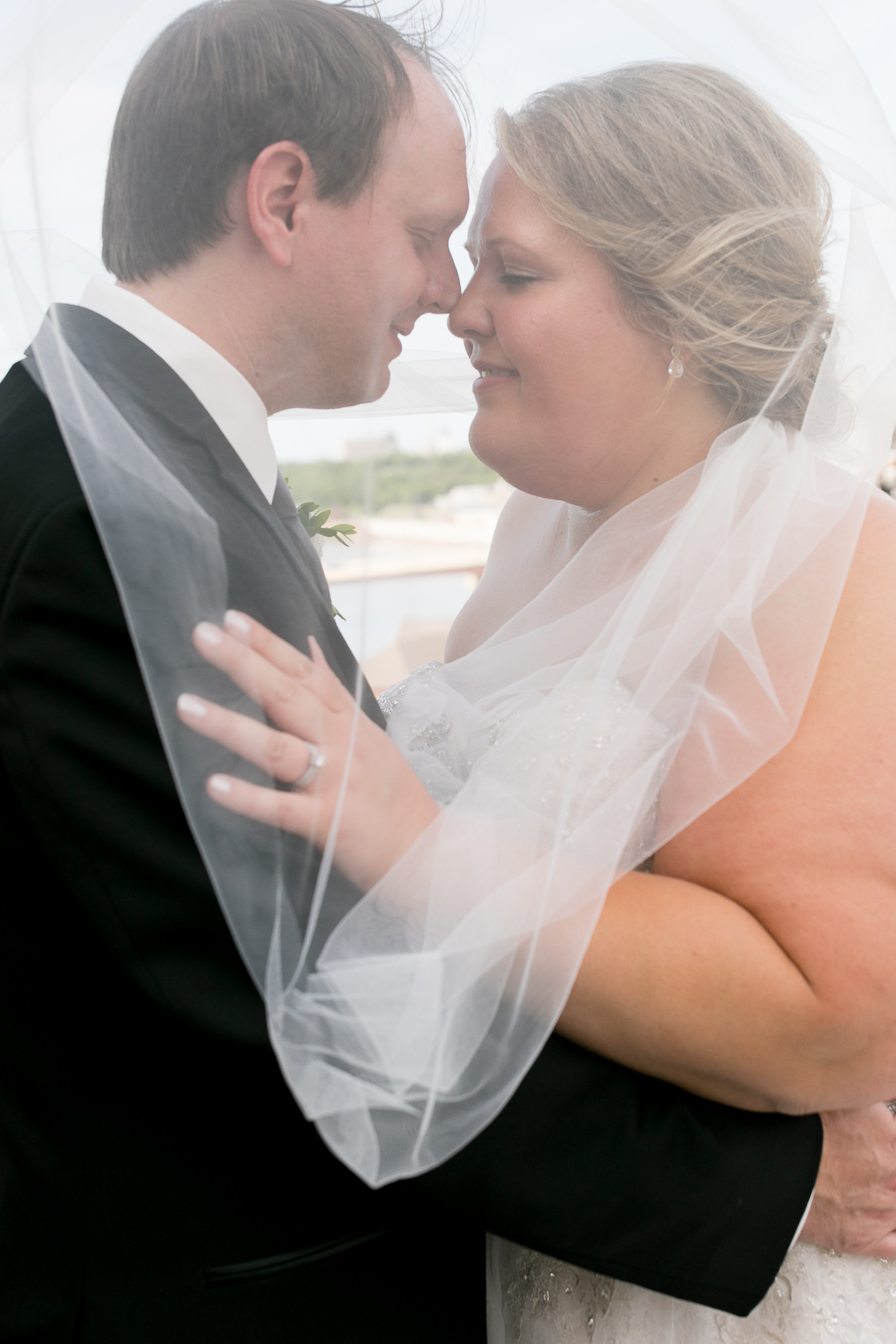 Alice HQ Photography | Bride and groom wrapped in the veil | beautiful plus size model with tear drop earrings