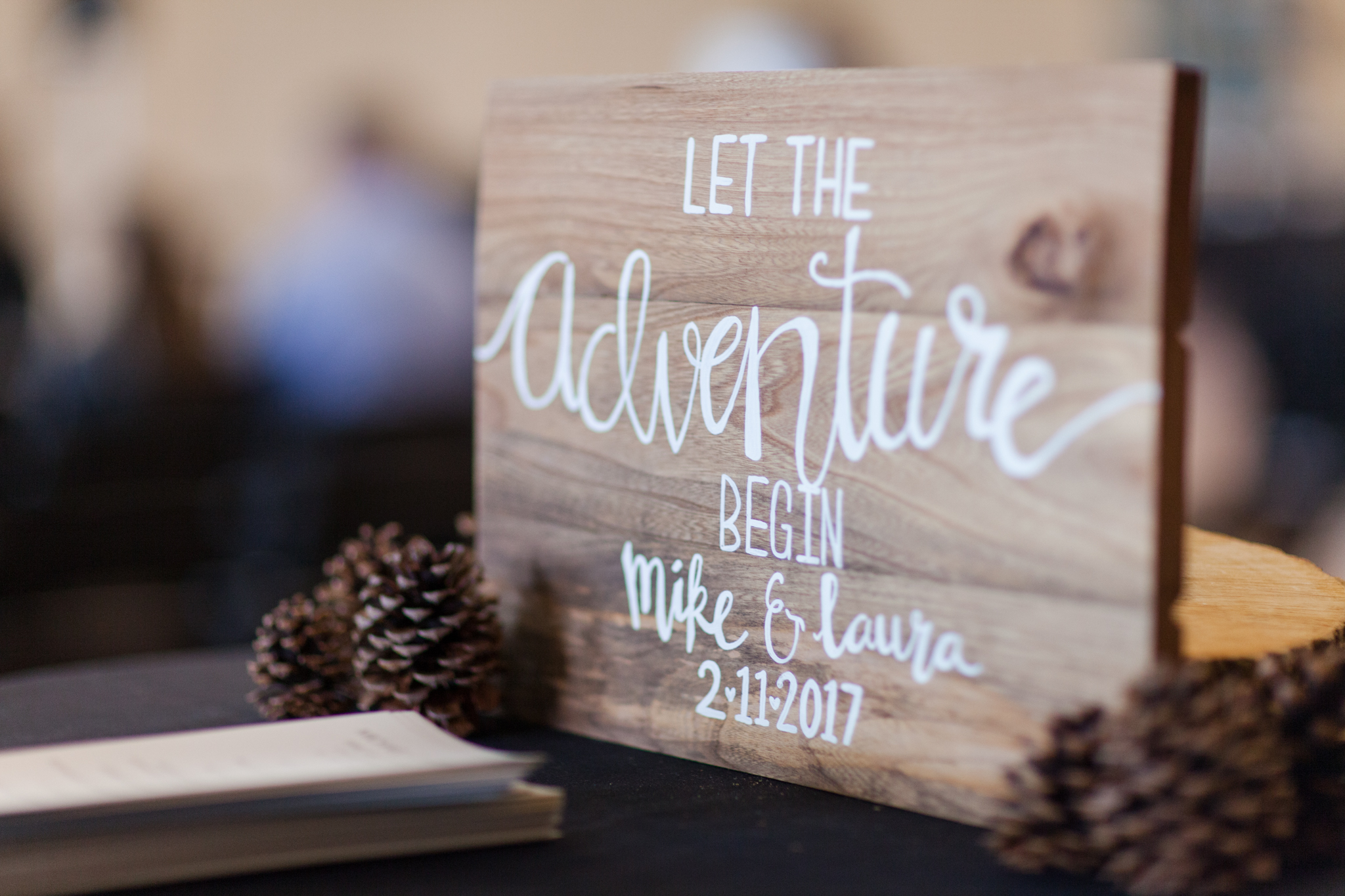 wood welcome sign 'let the adventure begin' pinecone decor | program table  | Sixpence Events & Planning | Jessa Anderson Photography | winter wedding