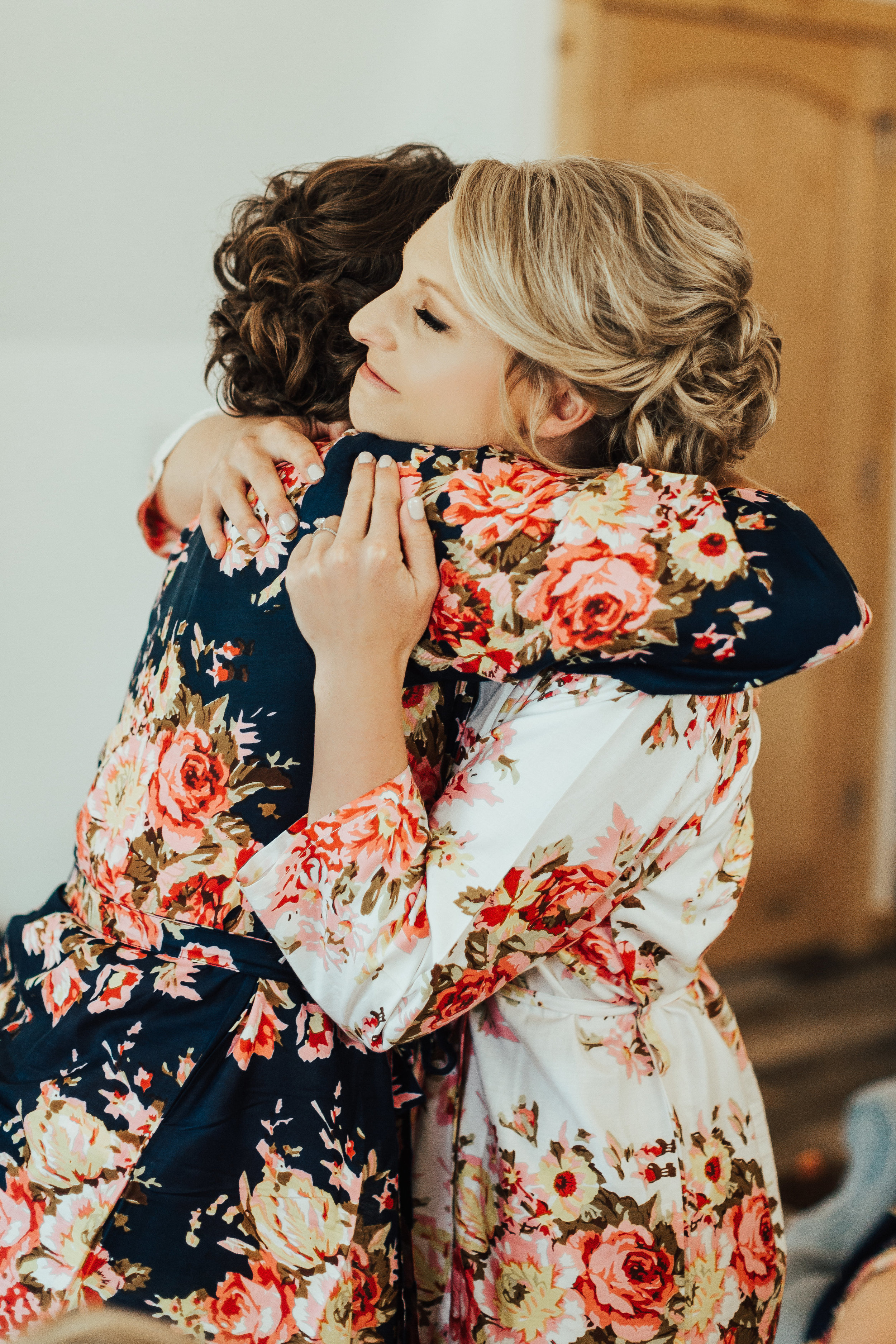 bride and bridesmaid hugs in matching robes | Janelle Elise | Megan + Corey | Furber Farm | Sixpence Events | A Vintage Touch Weddings23.jpg