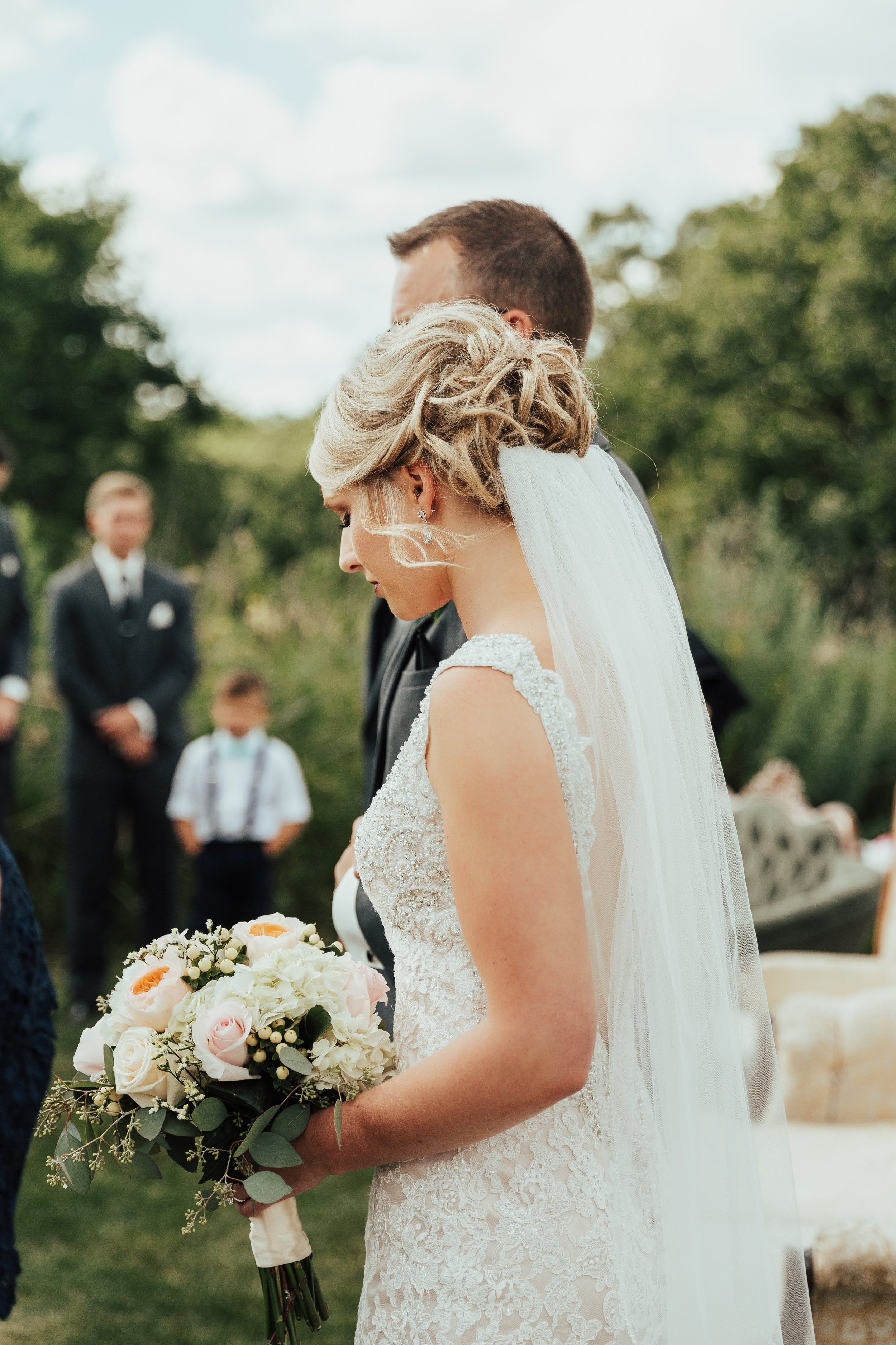 bride walking to the altar with his dad, veil tucked under her low bun | Janelle Elise | Megan + Corey | Furber Farm | Sixpence Events | A Vintage Touch Weddings103.jpg