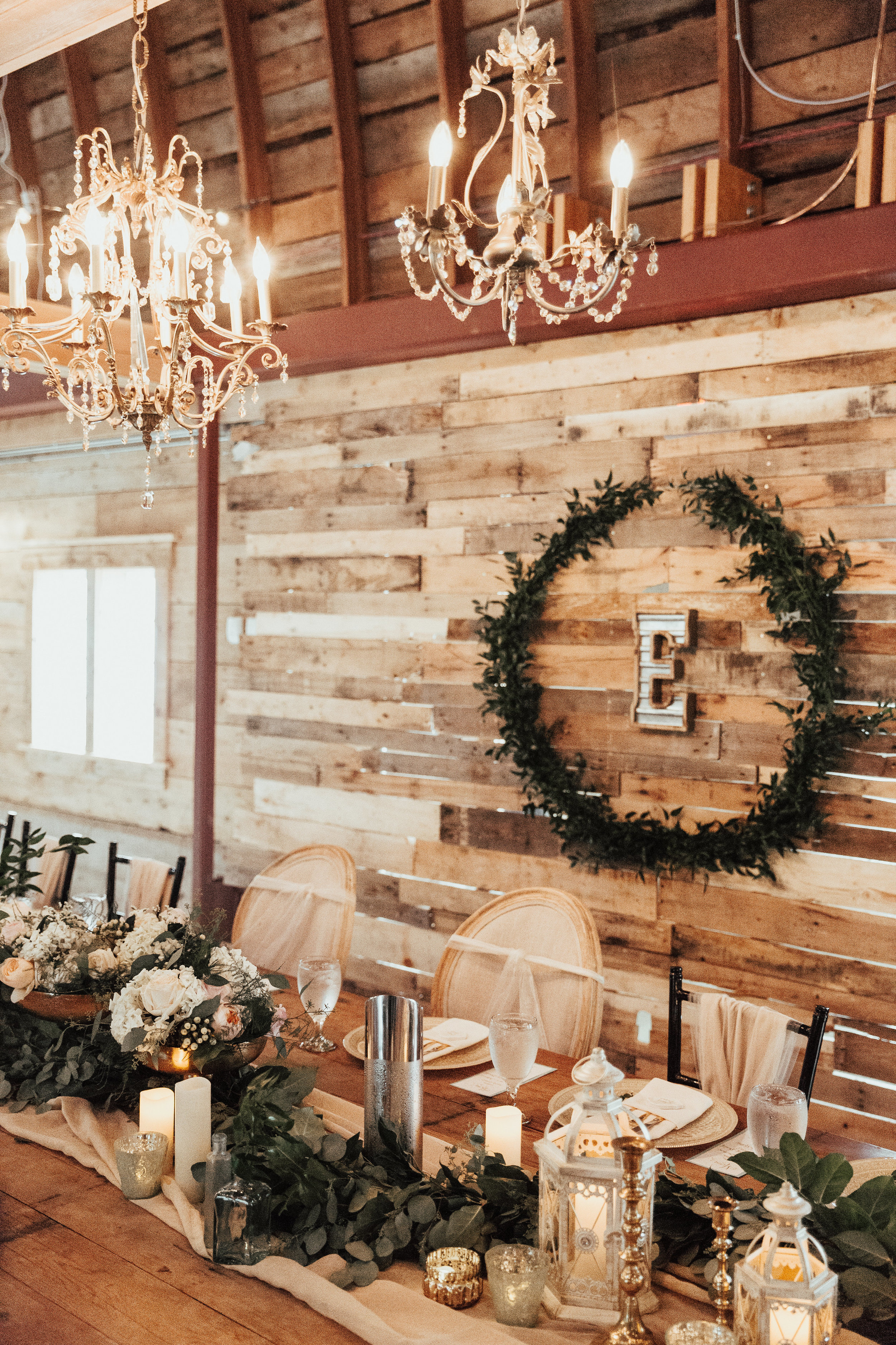 barn wood wall | green wreath with last name letter | barn chandeliers | custom runner decor with lanterns and votives and compotes | Janelle Elise Photography | Sixpence Events day of coordinating | wedding blog | wedding planned and rentals by A Vintage Touch Weddings