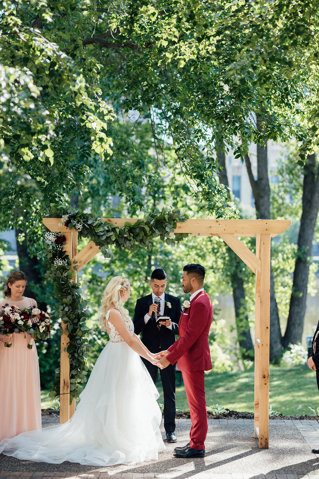 married under a wood arbor with simple green garland on the corner | Aaron T Photography | Nicollet Island Pavilion | Sixpence Events & Planning wedding blog