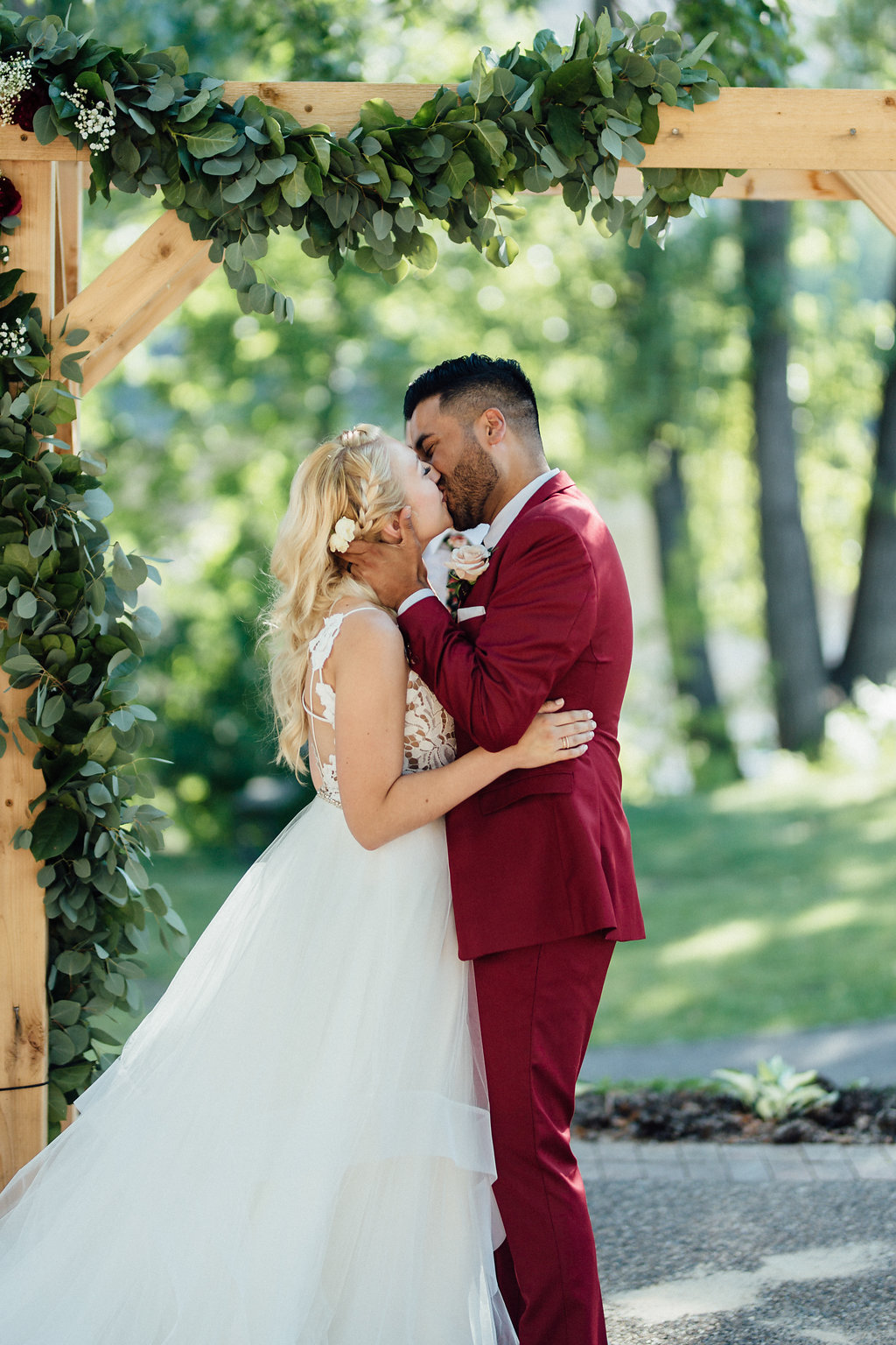 first kiss as husband and wife  | Aaron T Photography | Nicollet Island Pavilion | Sixpence Events & Planning wedding blog | groom in a red suit | bridal braid with lace top | wood arbor with green garland on the corner