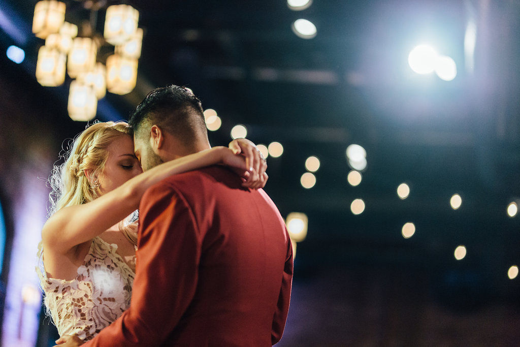 first dance | groom in red suit | toned bride arms | lace wedding dress top  | Aaron T Photography | Nicollet Island Pavilion | Sixpence Events & Planning wedding blog