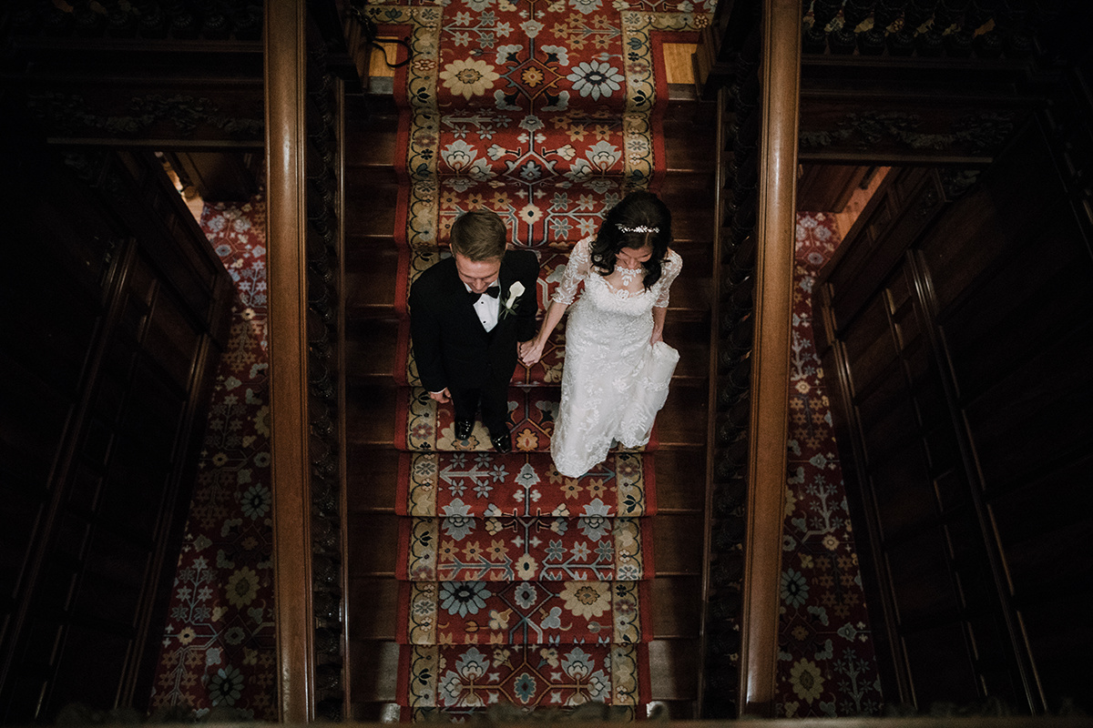 Bride and groom on the staircase at Turnblad Mansion  | Brian Bossany Photography | Sixpence Events & Planning wedding blog and day of coordinating | bridal tiara | bridal gown with lace sleeves | groom in bowtie