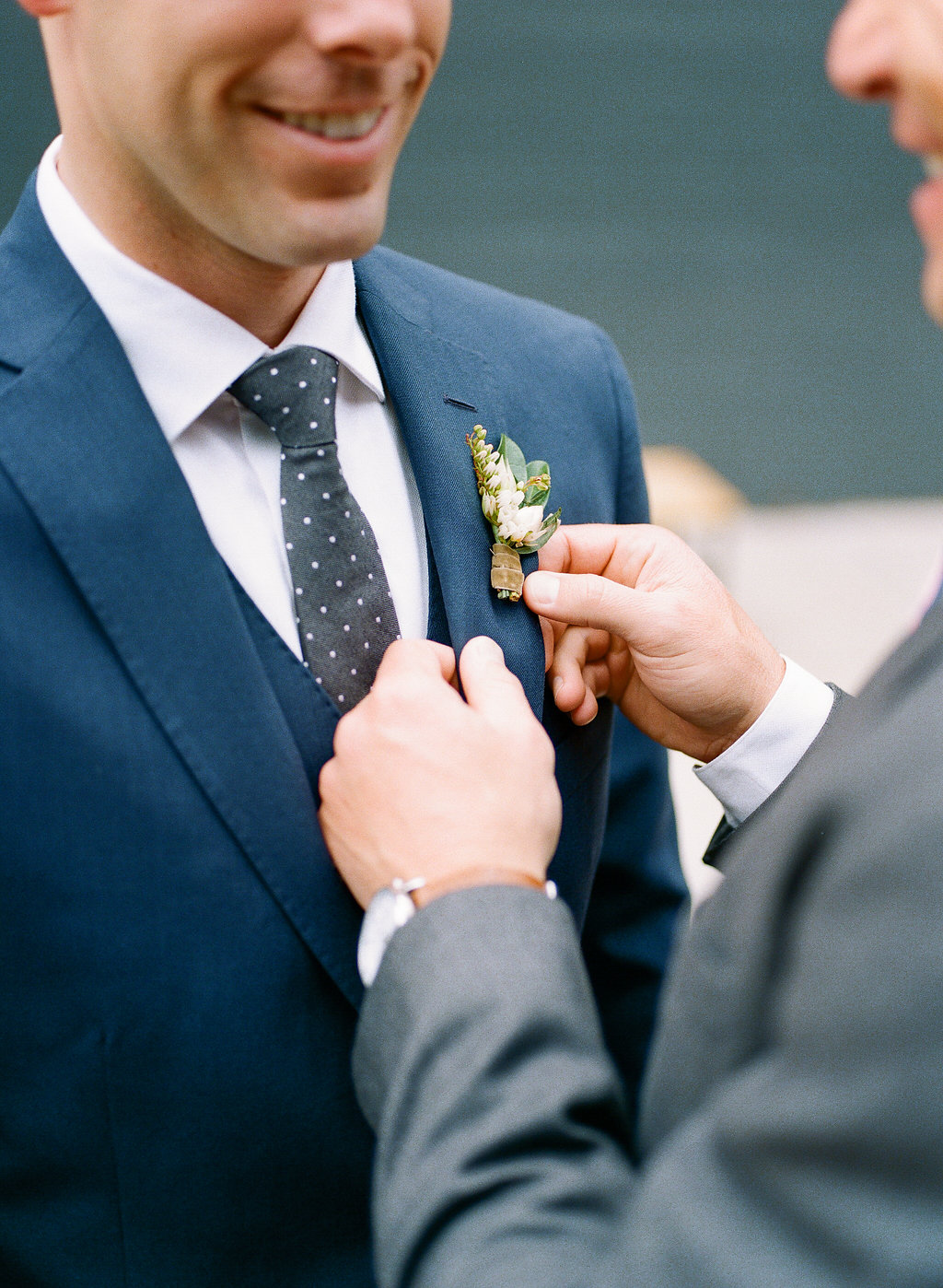 groom pinning boutonniere on his groom
