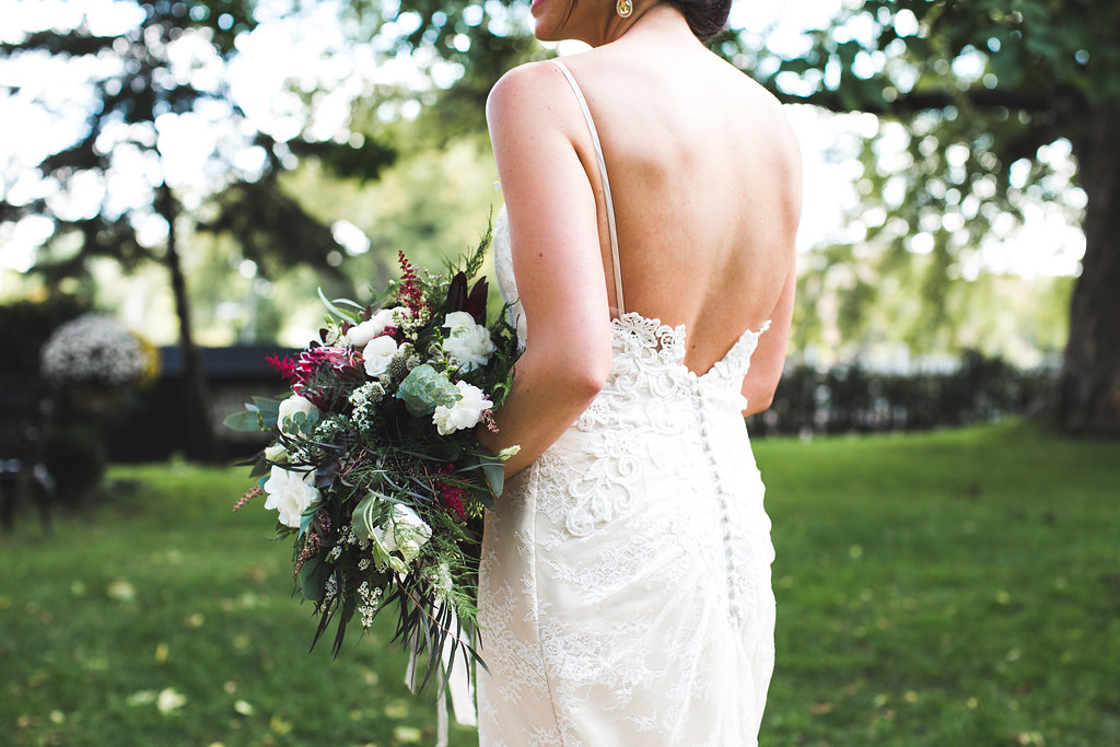 strapped wedding dress with low back and buttons   bridal bouquet with astilbe and eucalyptus