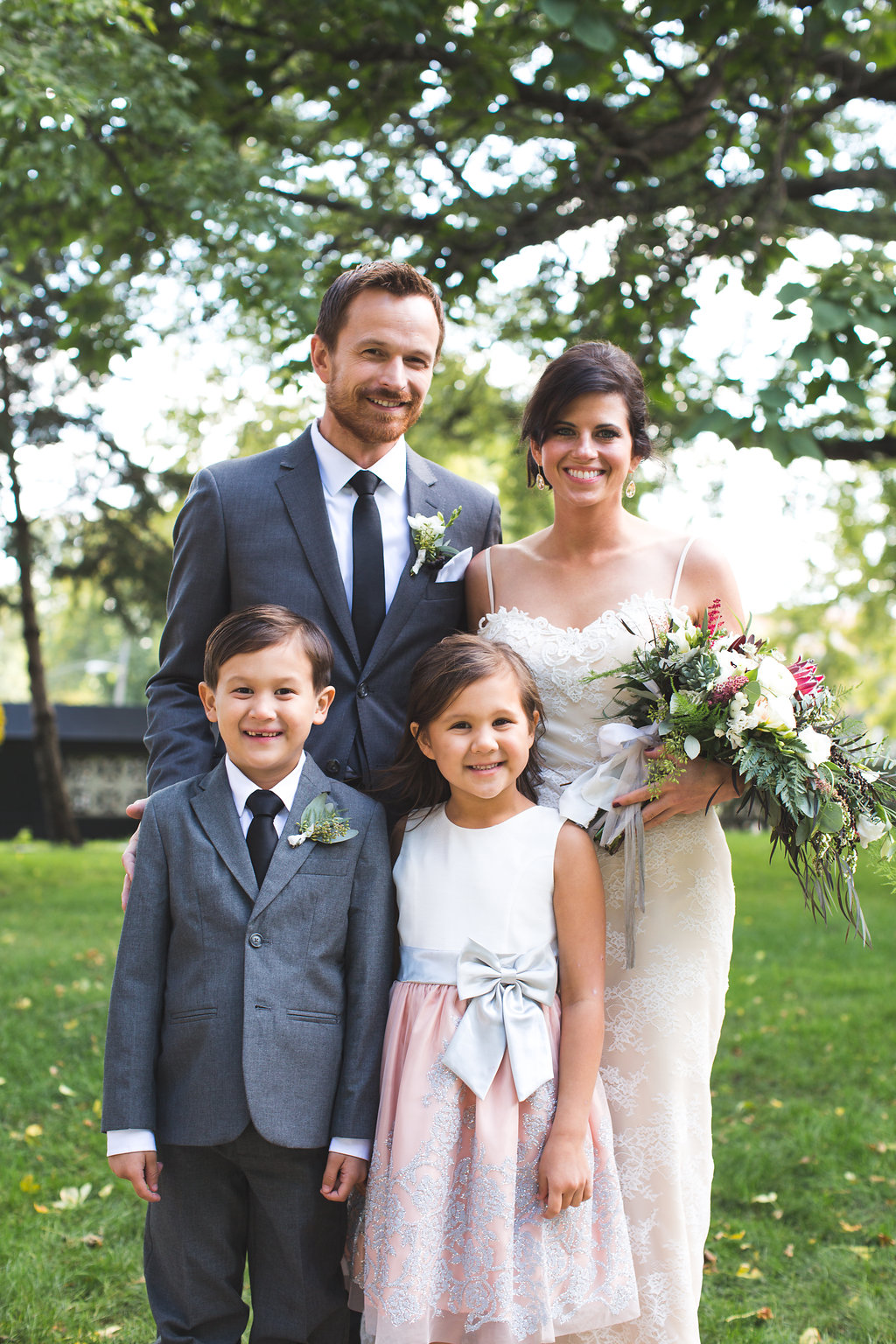 flower girl and ring bearer in mini bride and groom outfits   Annunciation church wedding   bride cradling bouquet   groom with scruff