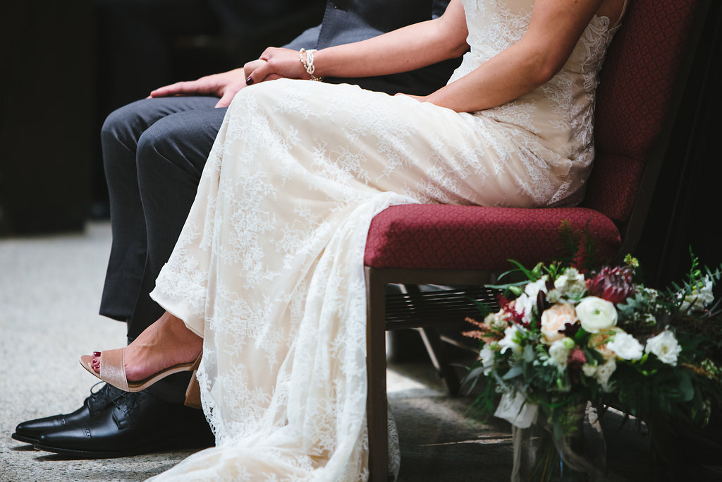 bride and groom sitting during the homily   Annunciation Church Minneapolis wedding   Aaron Rice Photography   Sixpence Events wedding planning