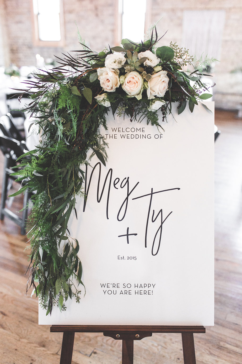 wedding welcome sign on an easel with a big greenery wreath overlaid