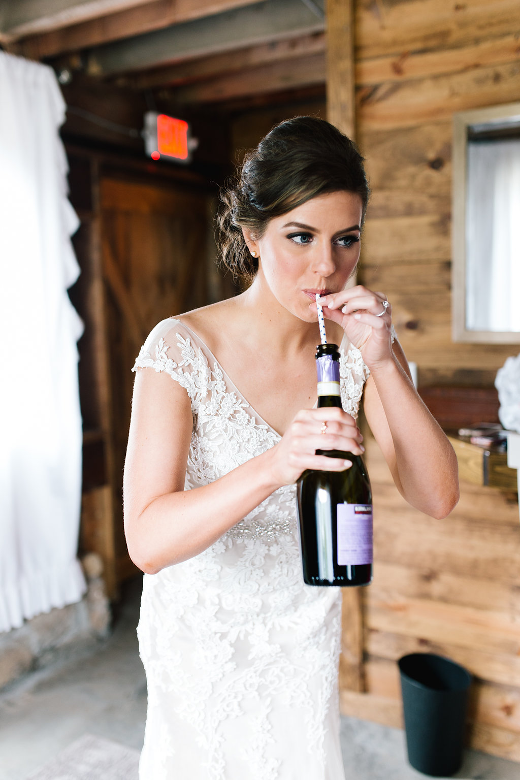 Jade + Seth Wedding | Allison Hopperstad Photography | Bloom Lake Barn | bride in cap sleeve lace dress | sipping champagne out of the bottle with a straw | Sixpence Events and Planning Day of Coordinating | A Vintage Touch wedding design and planning