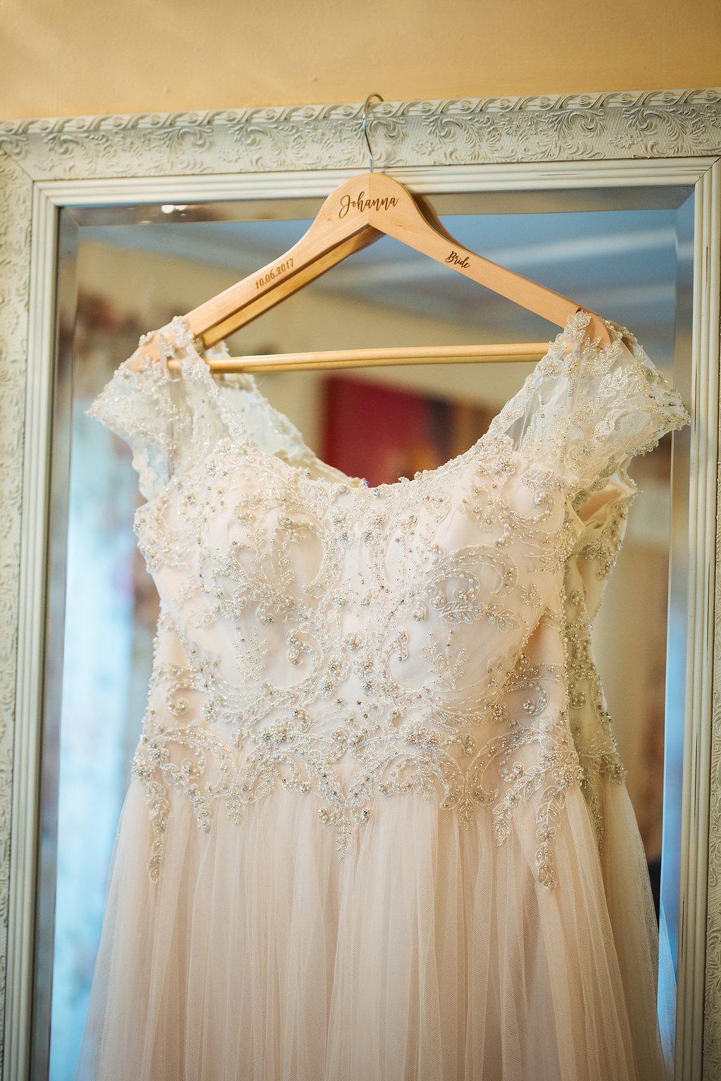 Julia + Johanna | Alyssa Lee Photography | Camrose Hill Flower Studio | details shot of bridal gown | soft pink tulle skirt with engraved wood hanger