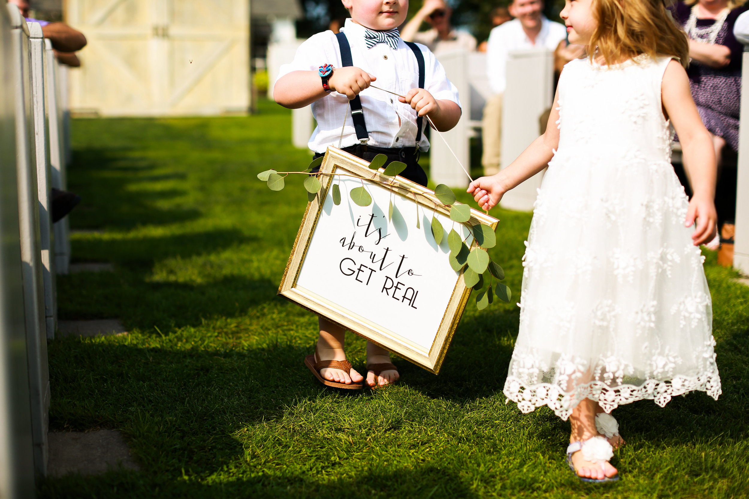 Jenna Kevin Wedding   Sixpence Events day of coordinating   Hannah Schmitt Photography   Legacy Hill Farm   flower girl and ring bearer twins holding a sign it's about to get real with gold frame and eucalyptus