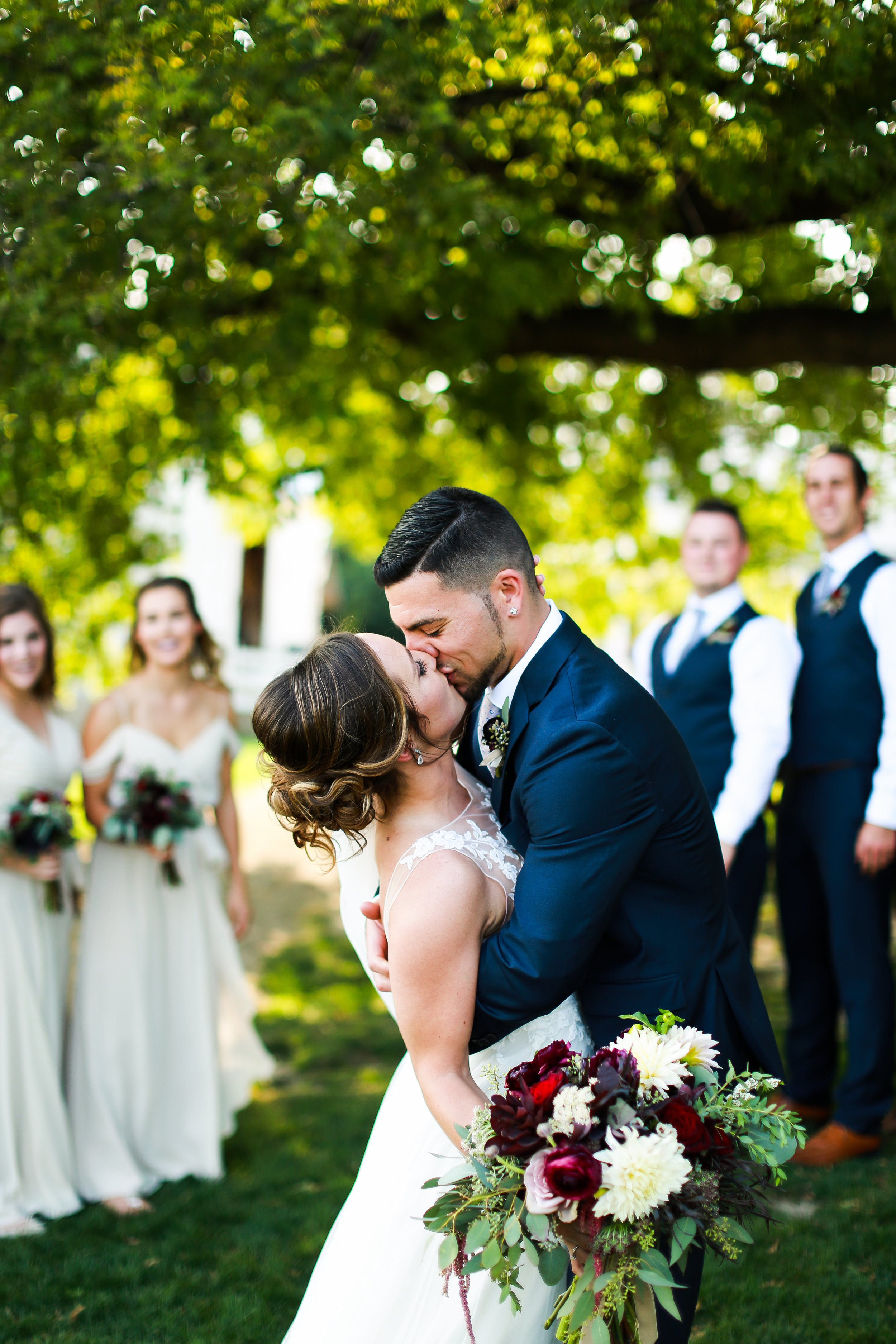 Jenna Kevin Wedding   Sixpence Events day of coordinating   Hannah Schmitt Photography   Legacy Hill Farm   bride and groom photos with bridal party kiss dip