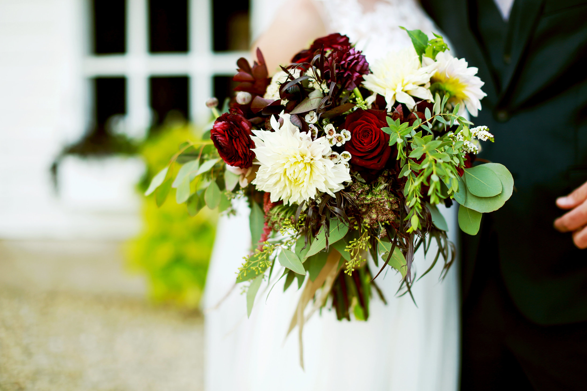 bridal bouquet with wax flowers and ranunculus, myrtle, chocolate queen anne's lace, seeded eucalyptus, and deep red flowers