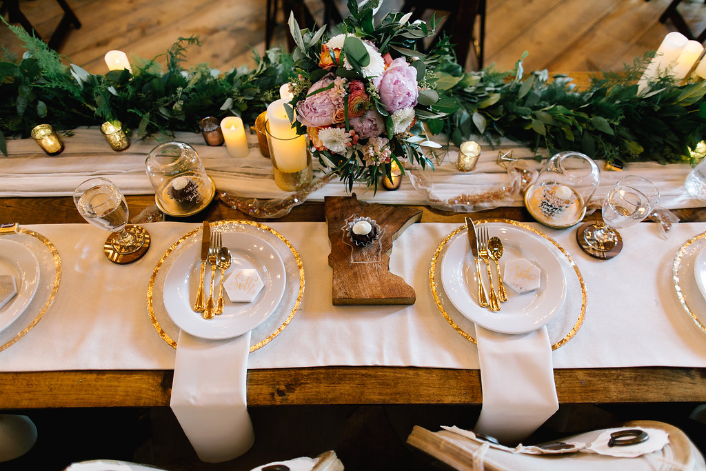 Jade and Seth Bloom Lake Barn wedding | Allison Hopperstad Photography | A Vintage Touch Weddings planning nad design | Day of Coordinating by Sixpence Events | designed head table with minnesota butcher board, gold silverware, bunt cakes in jars | greenery runner