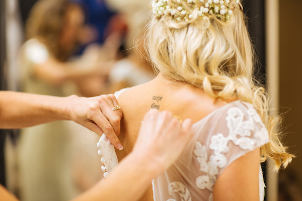 Hailey and Hunter | Alyssa Lee Photography | Sixpence Events & Planning | Bride putting on dress | baby's breath floral crown | carpe diem back tattoo
