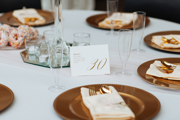 Hailey and Hunter | Alyssa Lee Photography | Sixpence Events & Planning | gold charger with off white napkin and gold plastic silverware | table number with menu by Champagne Press