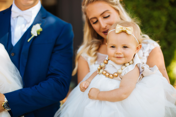 Hailey and Hunter | Alyssa Lee Photography | Sixpence Events & Planning | adorable flower girl with bow head band and big bead necklace in a tutu
